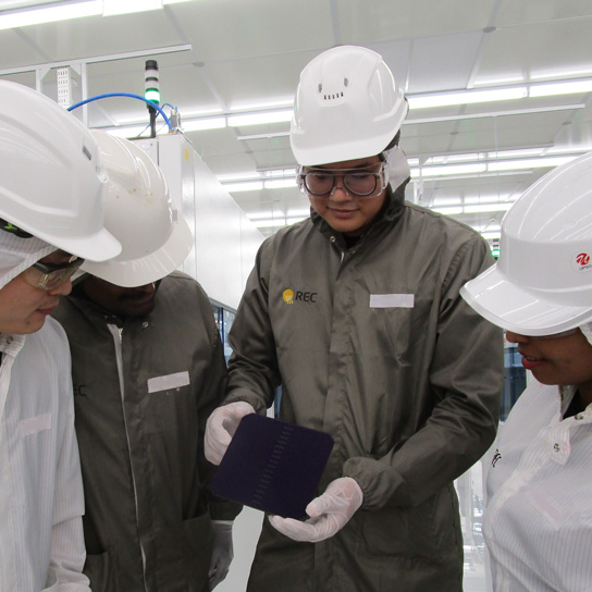 Four REC employees inspect a high-efficiency HJT solar cell at REC's state-of-the-art solar manufacturing facility in Singapore