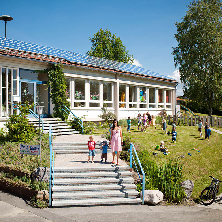 A female teacher with children in front of a kindergarten with a rooftop solar installation using premium REC solar panels