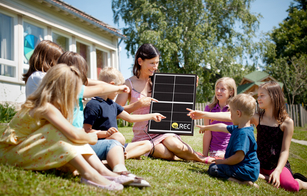 A group of children sitting on the grass point to an REC Alpha solar panel held by their teacher