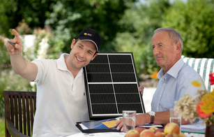 An REC Certified Solar Professional installer points to the sun and shows an REC Alpha solar panel to a customer interested in home solar